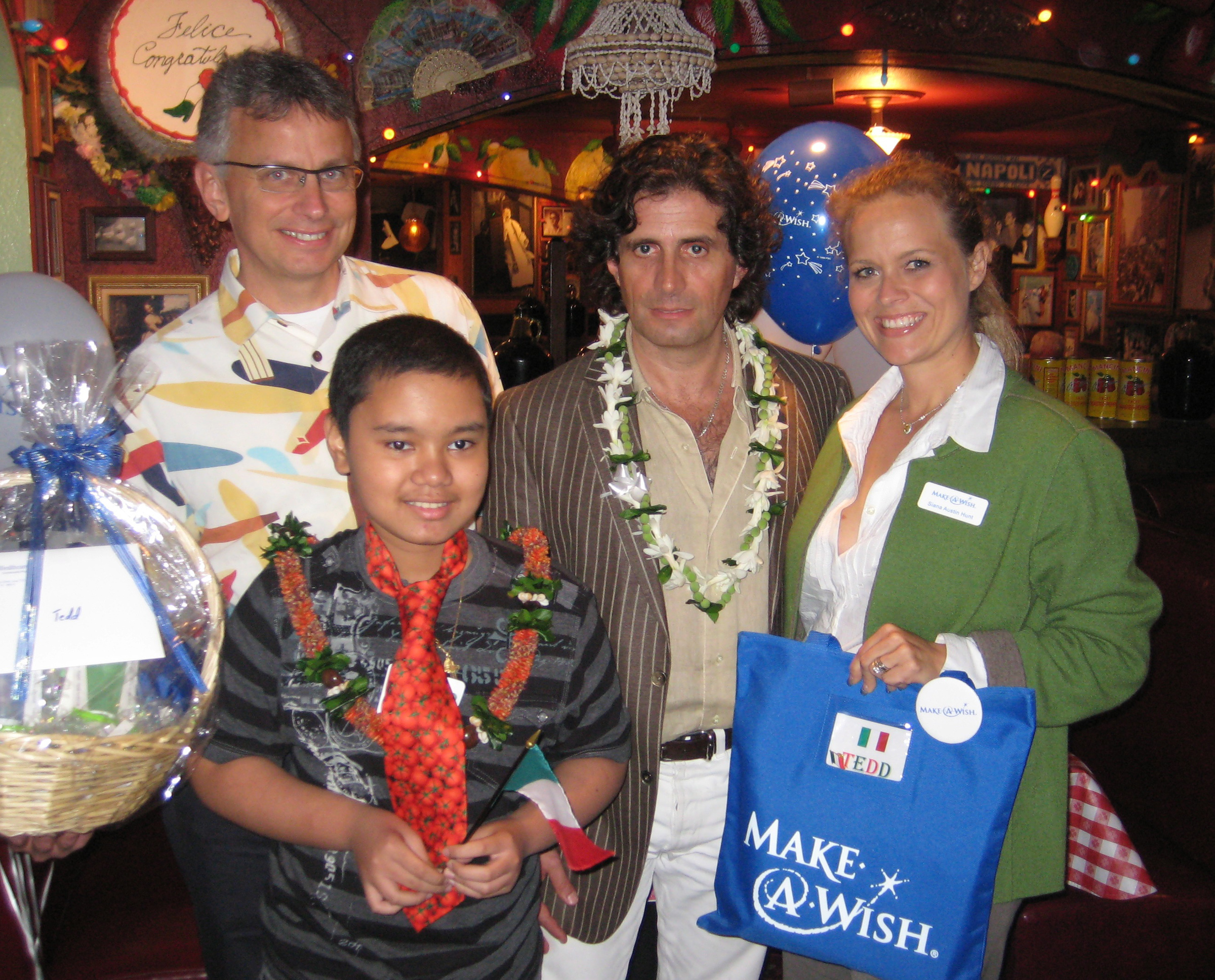 From left, UnitedHealthcare Hawaii Vice President David Heywood, Honorary Consul of Italy Dr. Michele Carbone and Make-a-Wish Hawaii executive director Siana Hunt presented 10-year-old Tedd of Honolulu with gifts at a send-off party at Buca di Beppo.