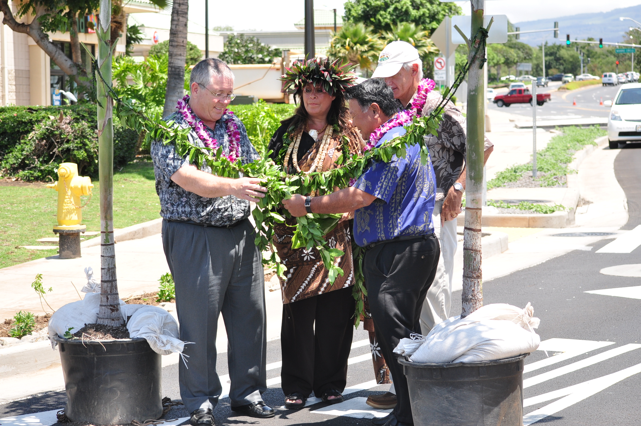 (L-R) Council member Don Couch, Kahu Alalani Hill, Mayor Alan Arakawa, and Public Works Director David Goode - Untying of the Maile lei to officially open the Kihei Roundabout at the intersection Pi`ikea Avenue and Liloa Drive.