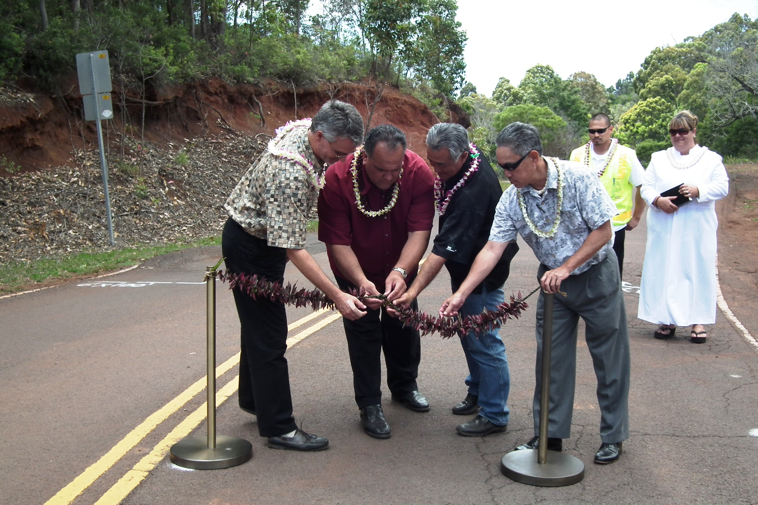 (L To R) County Engineer Larry Dill, Mayor Bernard Carvalho, Jr., Norman Shinno, island manager with Grace Pacific Corp, and County Councilman Dickie Chang untie the traditional lei following a blessing that marked the start of the Kokee Road enhancement project, while project manager Marween Ibanez and Kahu Jade Battad look on.
