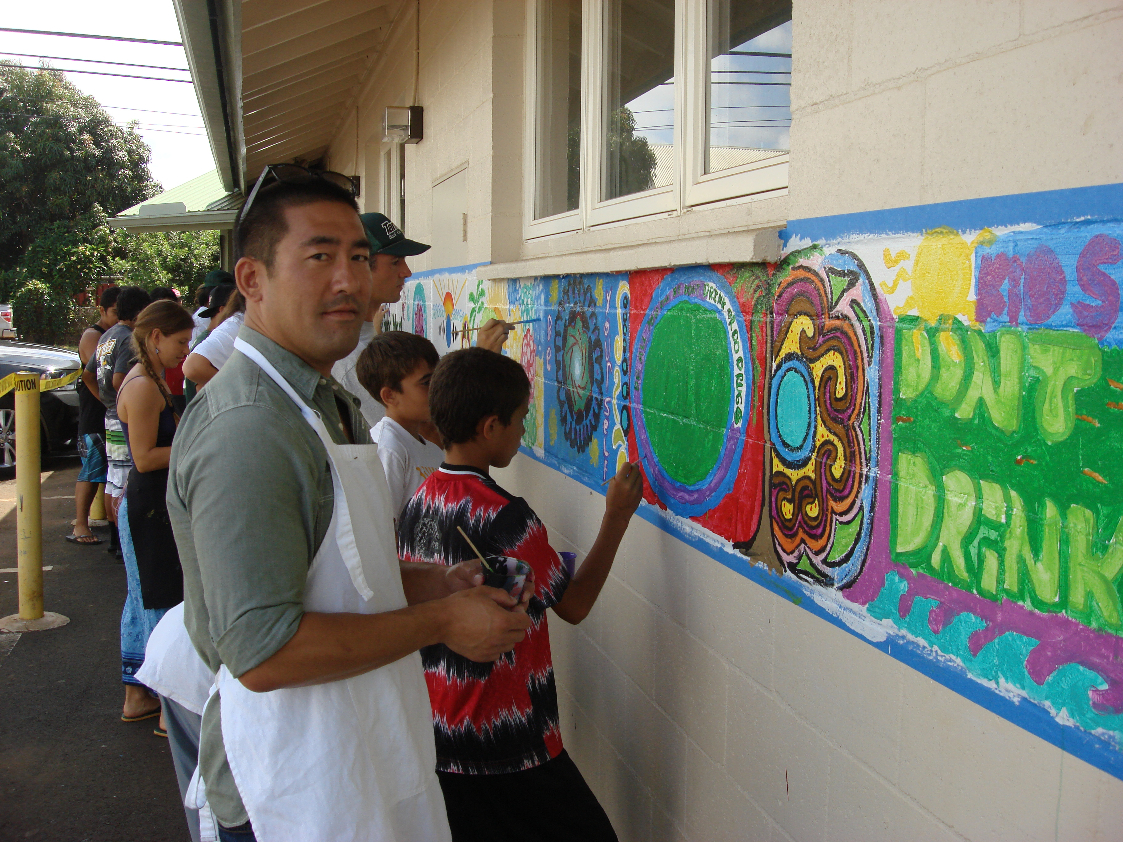 State Rep. Derek Kawakami pauses for a picture while painting a mural as part of a store makeover of Menehune Food Mart.