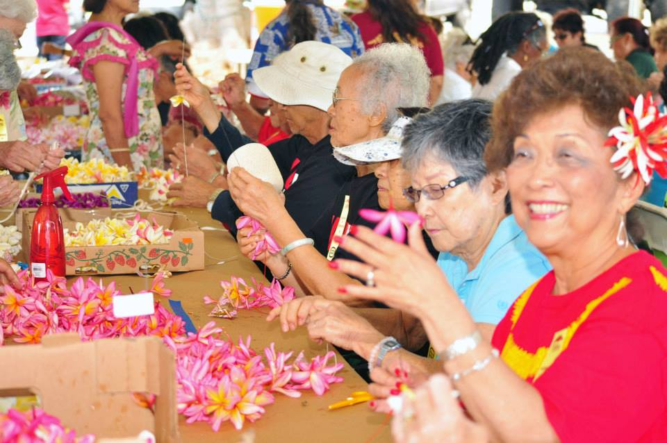"Community participants sew lei to honor veterans at the 2013 ""Blossoms for the Brave"" event. CREDIT: County of Maui"