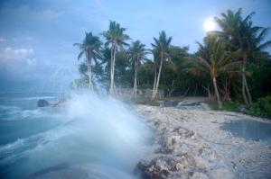 Waves crashing over roadway in Temwaiku, Kiribati. Credit, Annika Dean.