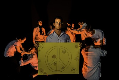 'Give peace a chance' (center Jackson Shimanoff with, starting left moving to the right: Catherina Chon, Eric Jabarri Combs, Noa Helela, Sorsha Scott-Holmes, Malia Galindo, Scott Peiterson, Austin Sunderman and Toby Carvahlo) Poet, played by Jackson Shimanoff protests the violence around him. Photos by Daniel Mayberry.